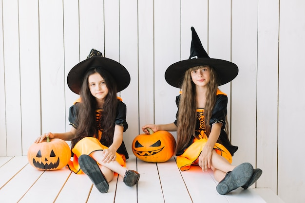 Little witches with pumpkins at halloween event