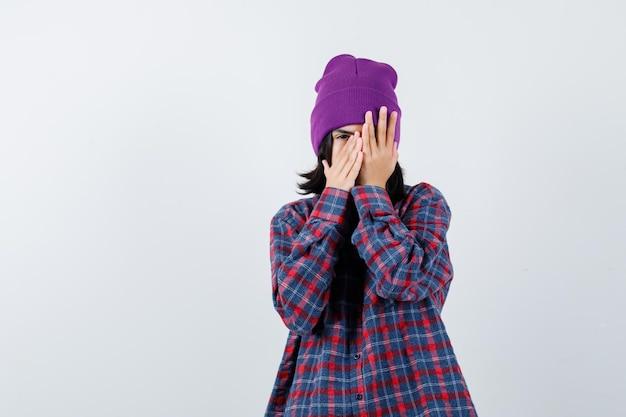 Piccola donna in camicia a scacchi e berretto che guarda attraverso e le dita sembrano spaventate