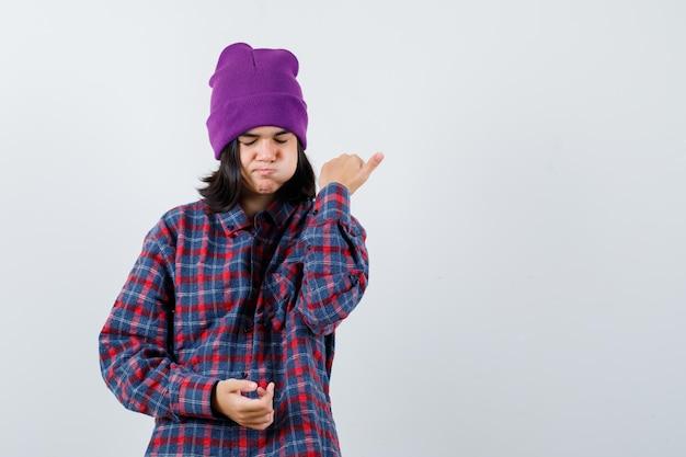 Piccola donna in camicia a scacchi e berretto che indica il pollice che sembra pensierosa
