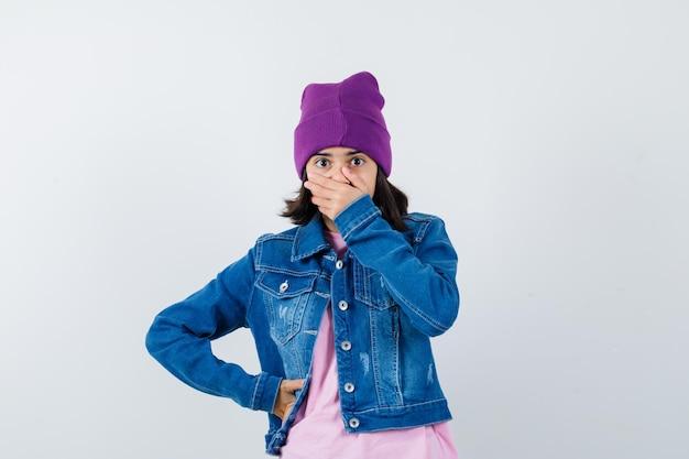Tシャツデニムジャケットで腰に手を保ちながら手で口を覆う小さな女性