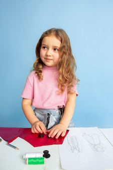 Маленькая женщина мечтает о будущей профессии швеи