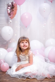 Little woman, in festive clothes and tiara, sits against balloons