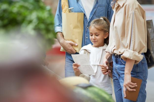 Маленькая женщина в продуктовом магазине с семьей