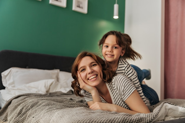 Little woman and her mother are lying on bed, laughing and looking into camera.