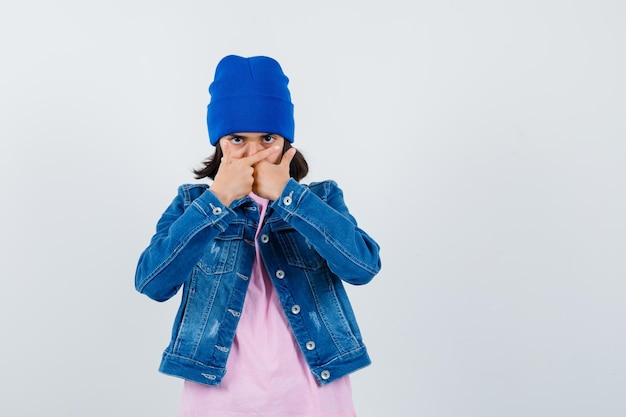 Piccola donna che tiene pistole a mano sulla bocca in maglietta e giacca di jeans che sembra seria