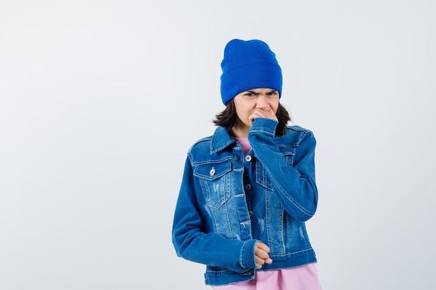 Piccola donna che tiene la mano sulla bocca in berretto con giacca di jeans t-shirt che sembra malinconica
