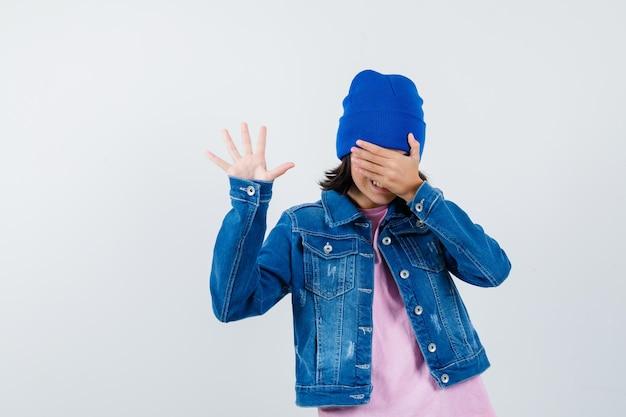 Маленькая женщина держит руку на лице, показывая ладонь и выглядит весело