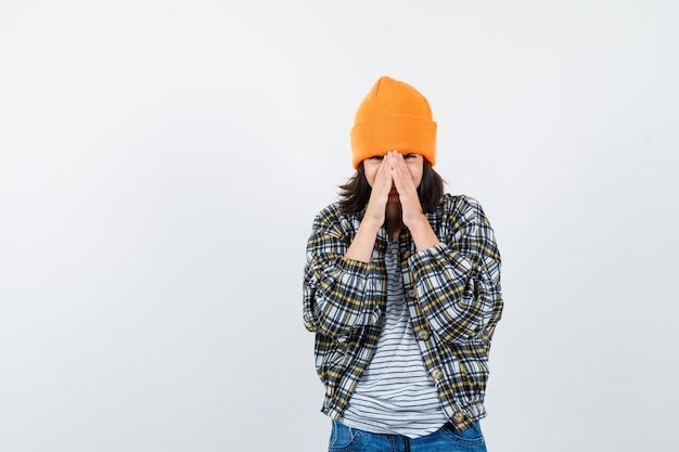 Piccola donna che si tiene per mano sul viso come tetto di casa in berretto giacca t-shirt che sembra felice
