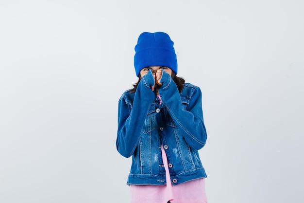 Piccola donna che si tiene per mano sul viso in maglietta e giacca di jeans