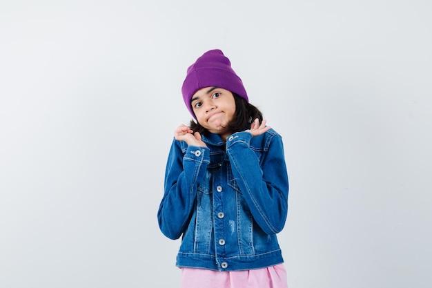 手のひらを広げて無力に見えるtシャツデニムジャケットビーニーの小さな女性