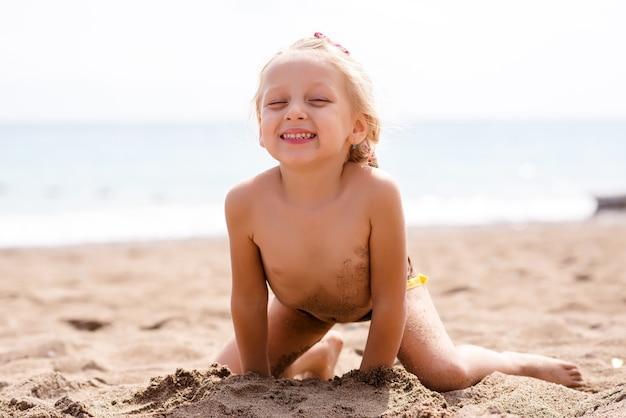 Маленькая женщина играет в песке у моря