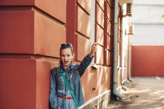 Little woman in jeans clothes stands near old red building