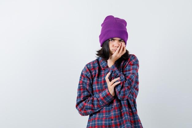 Piccola donna che si appoggia il mento sul berretto in mano che sembra seria