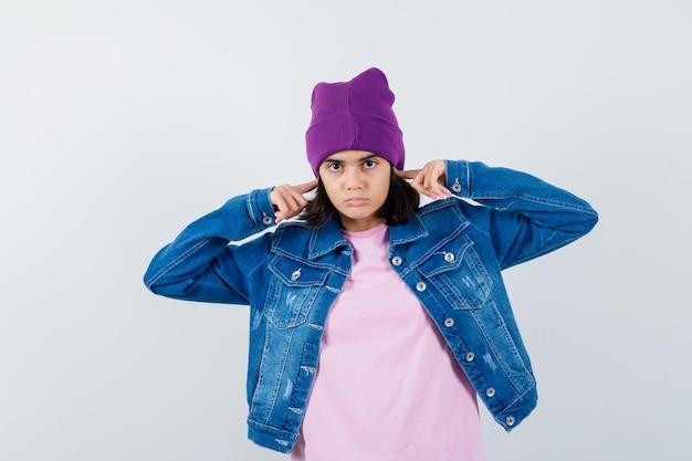 イライラしているように見えるtシャツデニムジャケットで指で耳を差し込む小さな女性