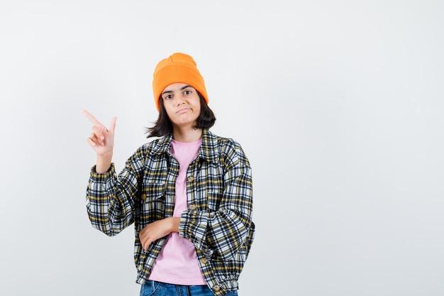自信を持って見えるtシャツジャケットビーニーの左上隅を指している小さな女性