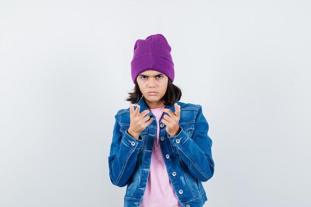 Piccola donna che punta alla telecamera in giacca di jeans e berretto che sembra seria