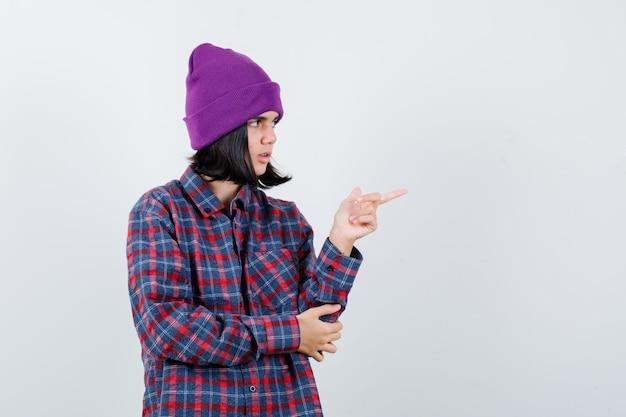 Piccola donna che indica il lato destro in camicia a scacchi e berretto che sembra sicura