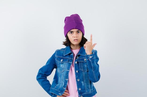 Piccola donna che indica in su in giacca di jeans e berretto che sembra perplessa