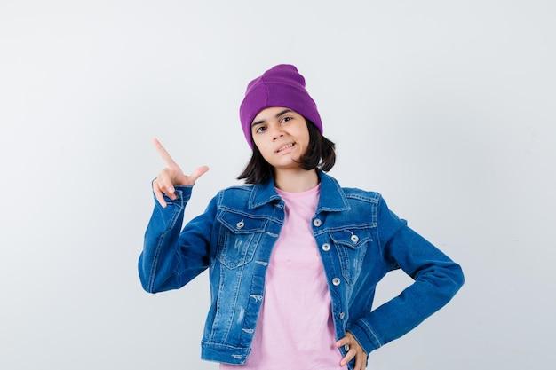 Piccola donna che indica l'angolo in alto a sinistra in giacca di jeans e berretto che sembra felice