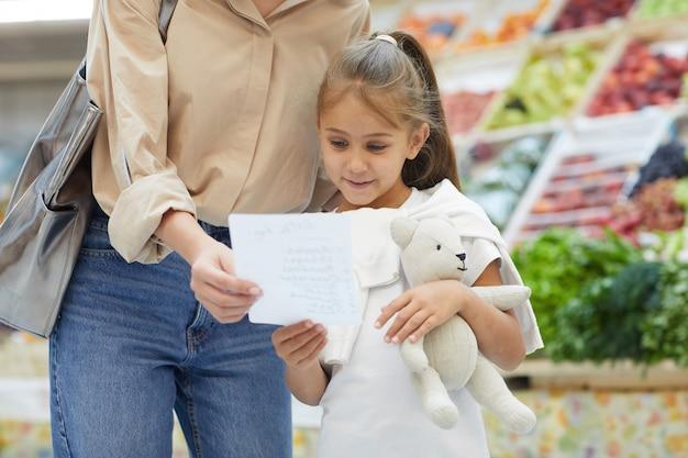 Маленькая женщина читает список покупок