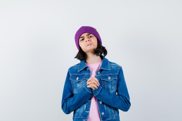 Piccola donna che mostra le mani giunte in un gesto di supplica che sembra speranzosa