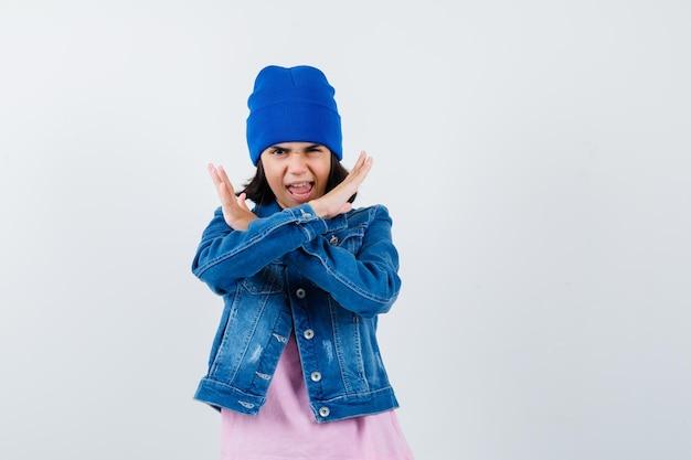 Маленькая женщина показывает жест стоп в джинсовой куртке и шапочке, выглядя испуганной