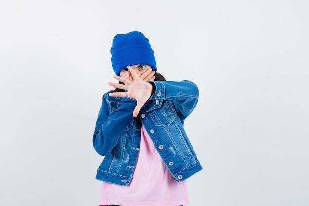 Piccola donna che mostra il gesto di arresto mentre copre la bocca con la mano nella giacca di jeans della maglietta
