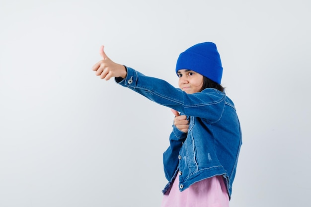 Piccola donna che mostra i pollici in berretto con giacca di jeans t-shirt e sembra allegra