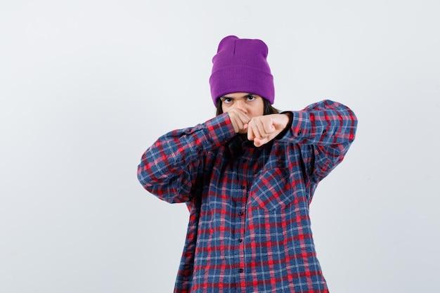 Маленькая женщина жалит в позе боя в клетчатой рубашке и шапочке, выглядя злобно