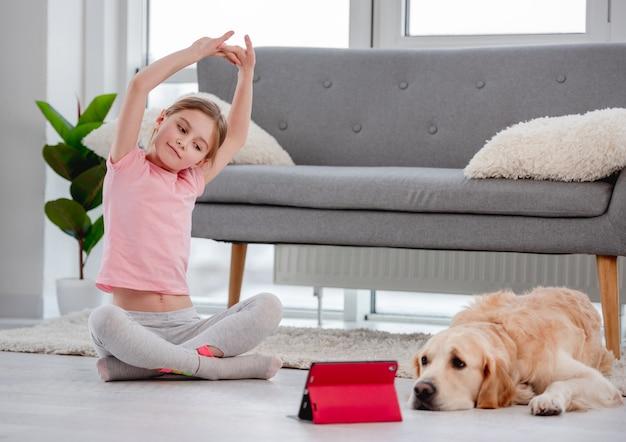 小さな女性は赤いタブレットと座ってオンラインヨガのレッスンで彼女の背中を伸ばします