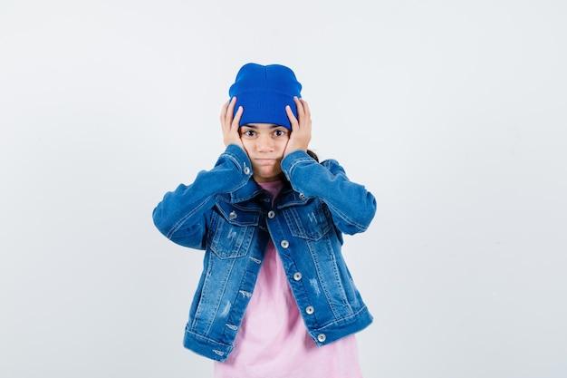 Piccola donna con berretto in giacca di jeans t-shirt che si tiene per mano sulla testa e sembra smemorata