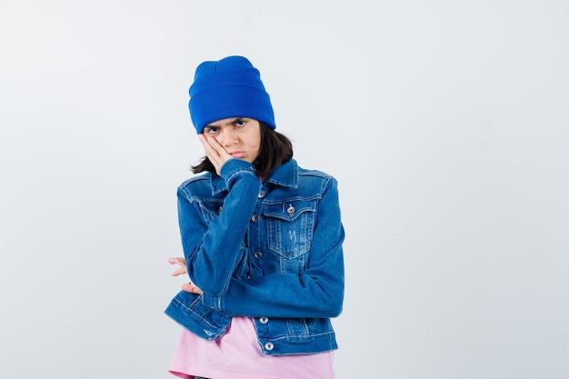 Piccola donna in t-shirt giacca di jeans berretto appoggiato sulla guancia con un'aria malinconica