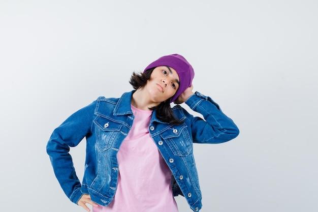 Piccola donna in t-shirt giacca di jeans berretto appoggiato la testa a portata di mano con aria stanca