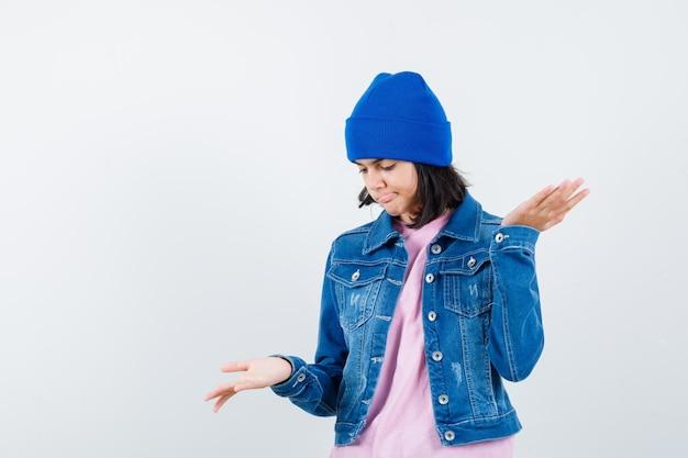Piccola donna con berretto in giacca di jeans t-shirt che fa un gesto con le squame che sembra esitante