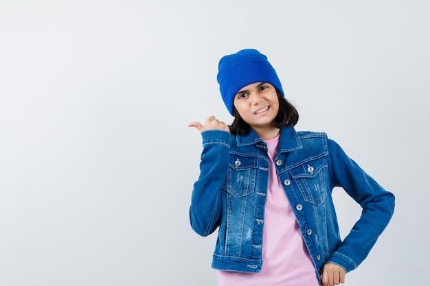 Piccola donna in t-shirt giacca di jeans berretto che punta il pollice in su