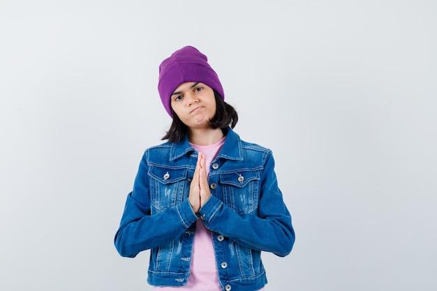 Piccola donna in giacca di jeans t-shirt che mostra il gesto di namaste che sembra speranzosa
