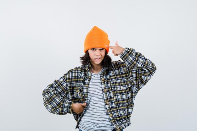 Piccola donna in t-shirt, giacca e berretto che indica la testa tenendo la mano sul fianco