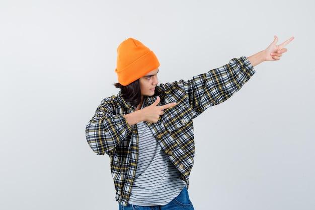 Piccola donna in berretto giacca t-shirt che punta nell'angolo in alto a destra