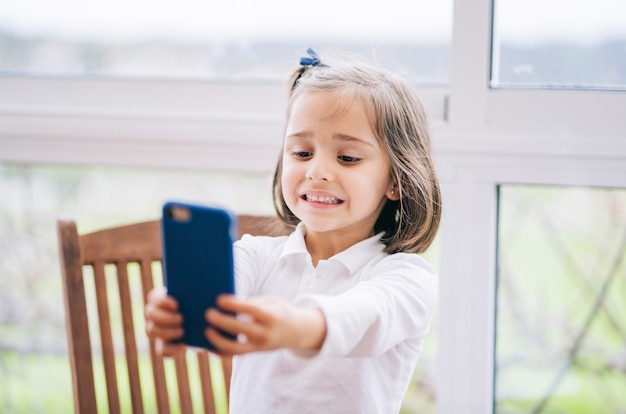 A little woman takes a picture with the mobile phone smartphone at home
