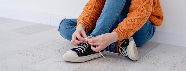 집에서 바닥에 앉아있는 동안 운동화에 신발 끈을 묶는 작은 여자