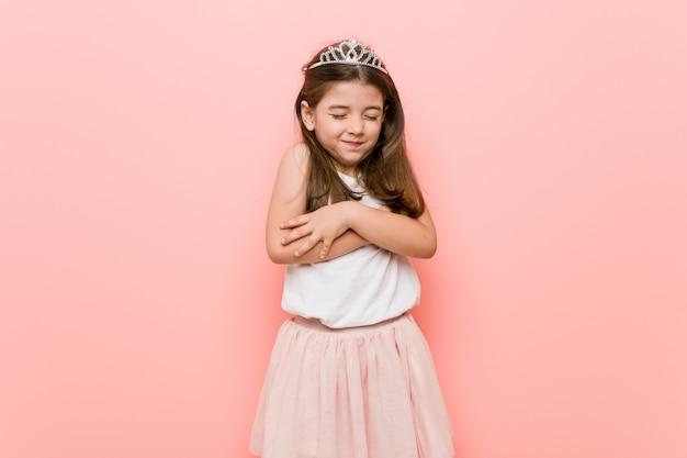 王女を着ている小さな女性のような抱擁、屈託のない、幸せな笑顔 Premium写真