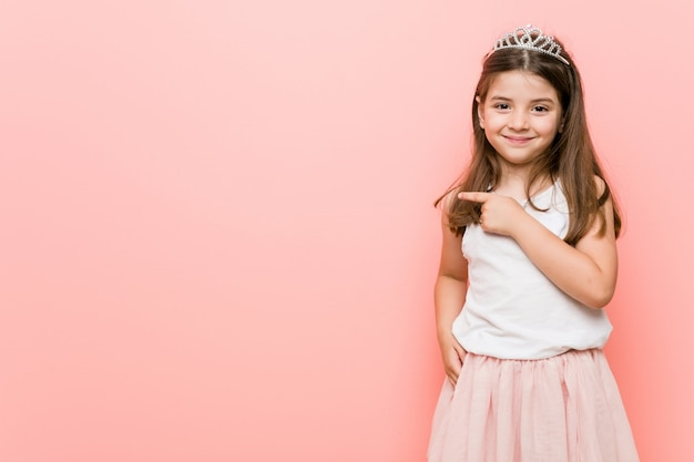 Little woman wearing a princess look smiling and pointing aside, showing something at blank space.