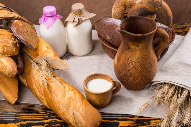 Little wooden cup of milk, tall pitcher with dried wheat grain stalks next to a wide assortment of bread products