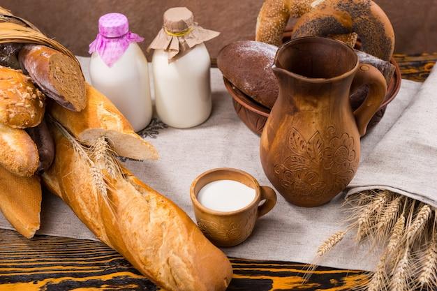 작은 나무 컵의 우유, 다양한 종류의 빵 제품 옆에 말린 밀 곡물 줄기가있는 키 큰 투수