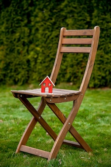 Little wooden house on a chair in a garden in spring