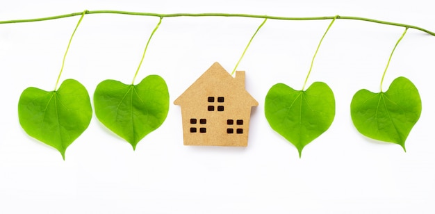 Little wooden house with green leaves heart shaped on white