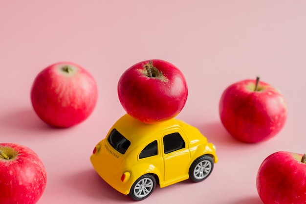 Little yellow bauble car with red apples on a pastel pink