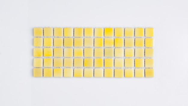 흰색 배경에 작은 노란색 세라믹 타일, 위쪽 전망, 마졸리카. 카탈로그