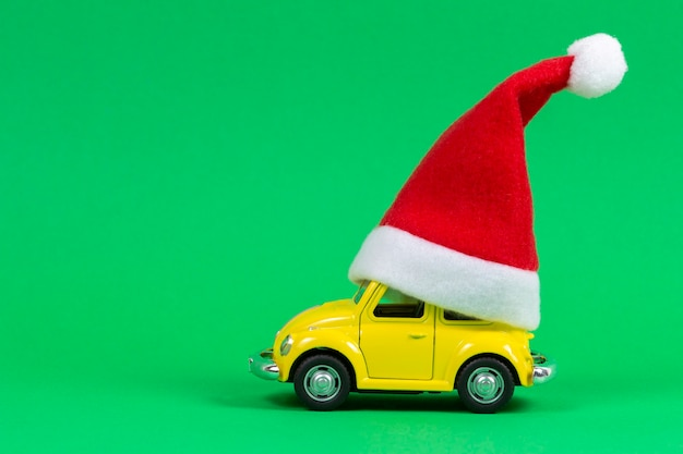 Little yellow retro toy model car with small red christmas santa claus hat on green