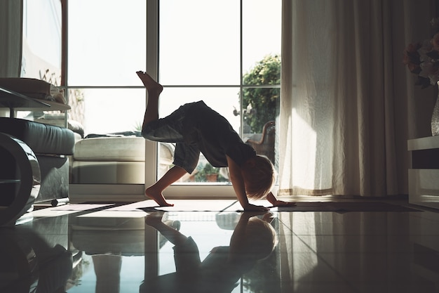 Little yogi child is practicing yoga indoors silhouette of cute child in downwardfacing dog pose